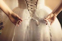 Toned photo of beautiful bride tying up her wedding dress Royalty Free Stock Images