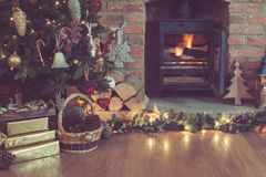 Christmas setting, decorated fireplace, fur tree. Toned photo of beautiful Christmas setting, decorated fireplace with woodburner, lit up Christmas tree with Stock Photos