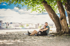 Toned photo of beautiful couple in love relaxing under tree Stock Images