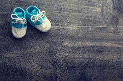 Toned photo of blue crocheted bootees. Stock Photos