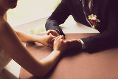 Toned photo of bride and groom holding hands at restaurant Royalty Free Stock Photos