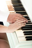 Toned photo of bride and groom wearing rings playing on piano Stock Images