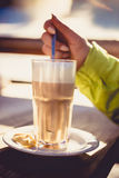 Toned photo of cappuccino on wooden table at ski resort cafe Royalty Free Stock Images