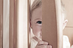 Cheerful and Sly Baby. Toned Photo of Cheerful and Sly Little Baby Playing Hide and Seek Stock Photos