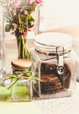 Toned photo of chocolate cookies in glass jar on kitchen table Stock Photos