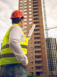 Toned photo of construction engineer pointing at building under Royalty Free Stock Photos