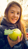 Toned photo of cute girl posing with green apple outdoors Stock Photography