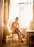 Toned photo of elegant bride getting dressed at hotel room Royalty Free Stock Images