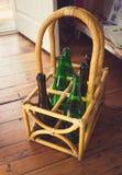 Toned photo of empty wine bottles in wicker basket on floor. Toned photo of empty wine bottles in wicker basket standing on floor Royalty Free Stock Photo