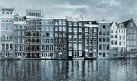 Toned photo of famous dancing houses of the Damrak canal in Amsterdam on sunset royalty free stock photography