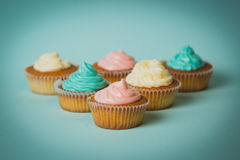 Toned photo of freshly baked colorful cupcakes on blue backgroun Stock Photography
