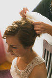 Toned photo of hairstylist attaching veil on brides hair Stock Photography