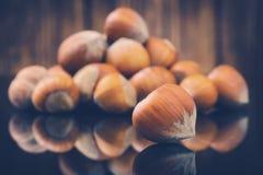 Toned photo of Hazelnuts, filbert on wooden. Toned photo of Hazelnuts, filbert on old wooden background Stock Photo