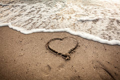 Toned photo of heart drawn on sand being washed by wave Stock Images