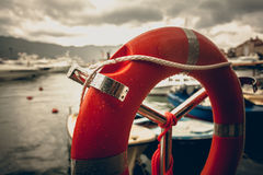 Toned photo of lifebuoy at rainy weather in seaport Royalty Free Stock Photos