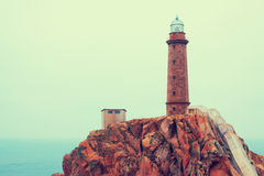 Toned photo with  lighthouse on  rocky coast Stock Image