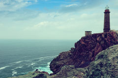 Toned photo with the lighthouse on the rocky coast Stock Images