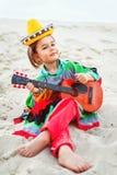 Toned photo of Little happy smiling boy plays his. Guitar or ukulele Royalty Free Stock Image