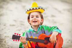 Toned photo of Little happy smiling boy plays his. Guitar or ukulele Royalty Free Stock Photography