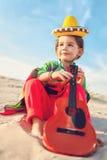 Toned photo of Little happy smiling boy plays his. Guitar or ukulele Stock Photo