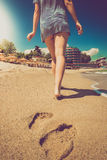Toned photo of lonely woman walking on the beach at sunny day Royalty Free Stock Image