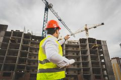 Toned image of male construction worker pointing at working cranes on building. Toned photo of male construction worker pointing at working cranes on building Stock Images