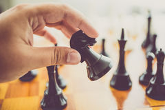 Toned photo of man making move with black horse at chess game. Closeup toned photo of man making move with black horse at chess game Royalty Free Stock Image