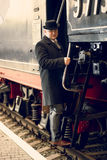 Toned photo of man in retro suit and bowler hat getting in train Stock Photography