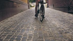 Toned photo of man riding bicycle on old street. Toned image of man riding bicycle on old street Royalty Free Stock Photography
