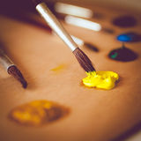 Toned photo of paintbrush dipping in vivid yellow oil paint Royalty Free Stock Image