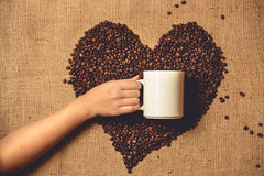Toned photo of person holding white mug against heart of coffee Stock Photography