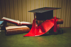 Toned photo of red ribbon and graduation cap on classic table Royalty Free Stock Photography