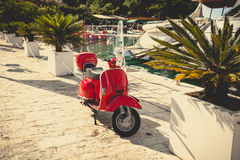 Toned photo of retro red scooter parked at port Stock Images