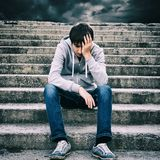 Sad Young Man outdoor. Toned Photo of Sad Young Man sit on the Stairs Royalty Free Stock Image