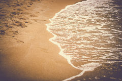 Toned photo of sea waves rolling on the sandy beach Royalty Free Stock Image