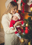 Toned photo of son in Santa costume and Smiling mother posing at Royalty Free Stock Photo