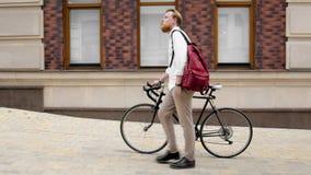 Toned photo of stylish bearded man with retro bicycle walking on street. Toned image of stylish bearded man with retro bicycle walking on street Stock Images