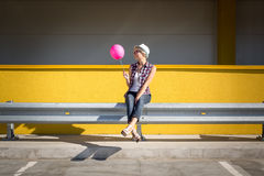 Toned photo of stylish hipster girl posing with pink balloon Stock Images