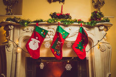 Toned photo of three red Christmas socks hanging on fireplace Stock Images