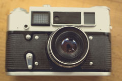 Toned photo from top of old retro film camera lying n table Royalty Free Stock Photo