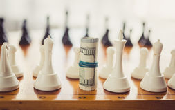 Toned photo of twisted money on board in place of chess piece Royalty Free Stock Image