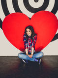 Toned photo of woman posing at studio with big red heart Stock Image