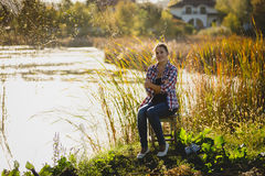 Toned photo of woman relaxing by the lake at sunset Stock Photography