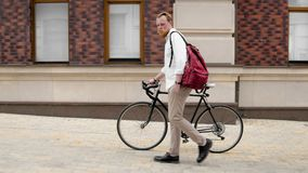 Toned photo of young man with bag walking with bicycle. Toned image of young man with bag walking with bicycle Royalty Free Stock Images