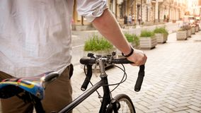 Toned photo of young man holding hands on bicycle while walking on street stock photo