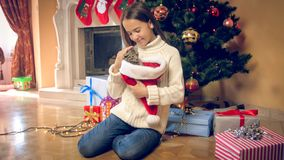 Toned image of young smiling girl caressing kitting under Christmas tree at house. Toned photo of young smiling girl caressing kitting under Christmas tree at stock image