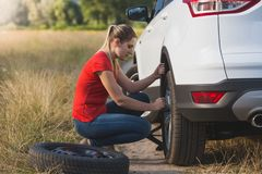 Toned image of young woman changing car flat tire with spare field in field. Toned photo of young woman changing car flat tire with spare field in field Stock Photos