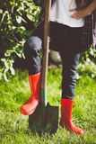Toned photo of young woman holding leg in rubber boots on shovel Stock Image