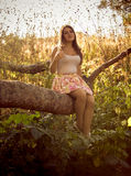 Toned photo of young woman sitting on big branch at foreast Stock Photo