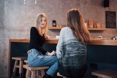 Toned picture of best friends having date in cafe or restaurant. Beautiful girls talking or communicating while drinking. Coffee Royalty Free Stock Image